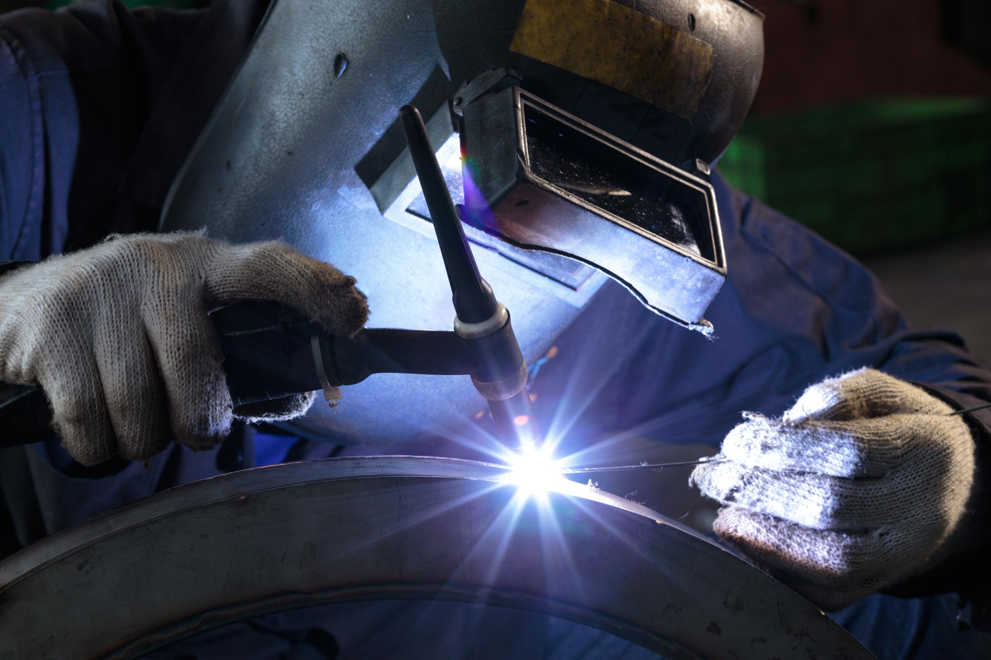 professional welder welding metal part